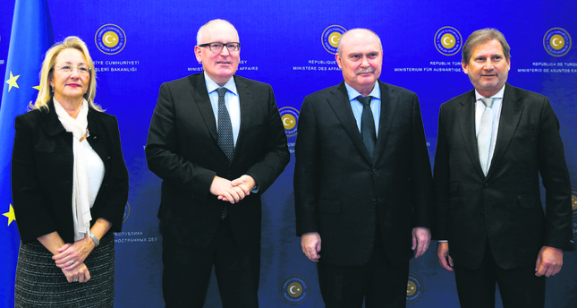 Turkey's EU Minister Dedeoğlu (L), European Commission First Vice President Timmermans (2nd L), Turkish FM Sinirlioğlu (2nd R) and EU Commissioner Hahn pose for cameras after a meeting in Ankara on Nov. 11.
