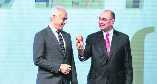 MÜSİAD Head Nail Olpak receives an apple from Yıldız Holding Vice Chairman Ali Ülker at the VİZYONER'15 Sectors Summit. The business world underlined the importance of sharing referring to President Erdoğan's statements.