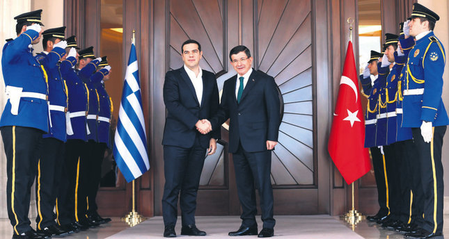 PM Ahmet Davutoğlu (R) shakes hands with his Greek counterpart Alexis Tsipras upon his arrival for a meeting in Ankara.