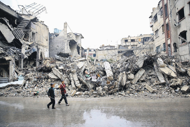 Syrian children walk past the rubble of destroyed buildings in Douma, an area held by moderate groups in the east of the Syrian capital Damascus.