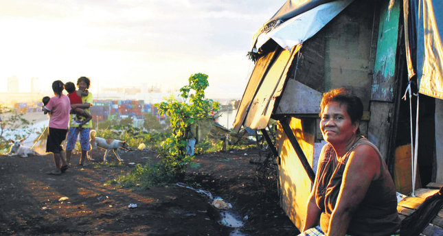 """Juanita Espinosa enjoys a sunset in front of her house in the slum """"Smokey Mountain"""" in Manila, Philippines. A few miles from the gleaming venue hosting U.S. President Obama and other world leaders sits Manila's slum of slums on a mountain of trash"""