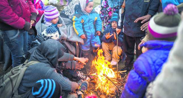 Refugees and migrants keep warm around a bonfire outside the registration and transit camp near Gevegelija, The Former Yugoslav Republic of Macedonia.
