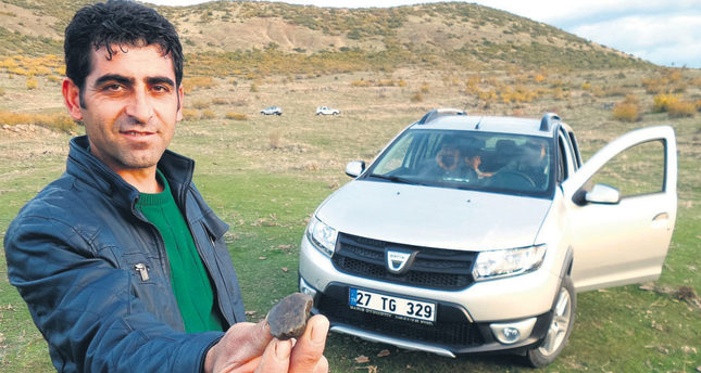 İsmail Ergin shows a meteorite and poses with the car he bought after selling another sizeable piece. (AA Photo)