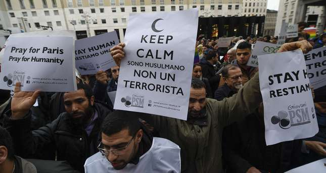 People hold placards during a demonstration of muslims to speak out against terrorism a week after Paris attacks, on November 21, 2015 in Milan. (AFP Photo)