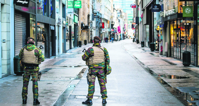 Belgian soldiers patrol Rue Neuve, the busiest shopping street in Brussels, now empty due to the terror alert level being elevated to 4/4.