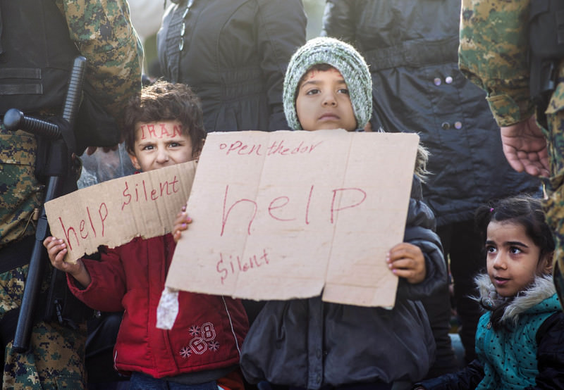 A child holds a notebook with a message reading ,help, as migrants and refugees from Iran sit on railway tracks while waiting to cross the Greek-Macedonian border near Gevgelija on November 24, 2015. (AFP Photo)