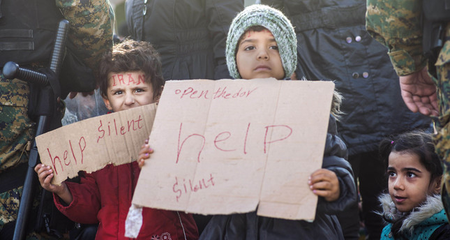 A child holds a notebook with a message reading help as migrants and refugees from Iran sit on railway tracks while waiting to cross the Greek-Macedonian border near Gevgelija on November 24, 2015. (AFP Photo)
