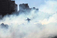 A Palestinian protester uses a sling as he prepares to return a tear gas canister fired by Israeli troops.