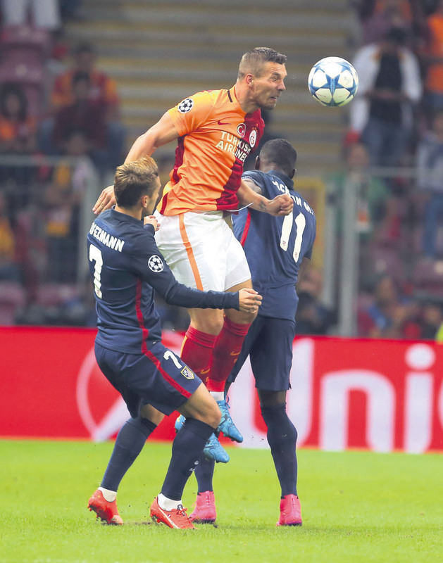 Galatasaray's Podolski (C), fights for the ball with Antoine Griezmann (L) and Jackson Martinez of Atletico Madrid during the Champions League.