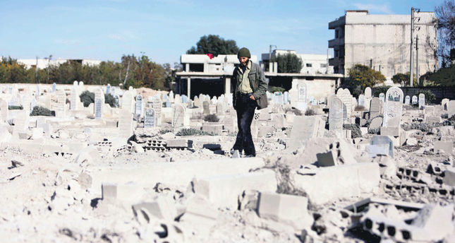A man walking in a graveyard of destroyed graves in a neighbourhood heavily damaged by Russian airstrikes in the moderate-held region of eastern Ghouta, Syria.