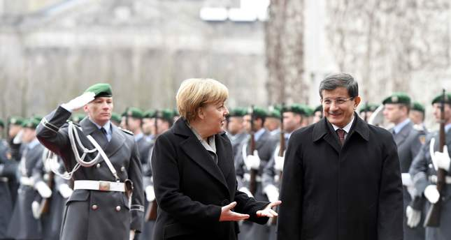German Chancellor Angela Merkel (L) and Turkish Prime Minister Ahmet Davutoglu (R) review a military guard of honour before their meeting at the Chancellery in Berlin, on January 12, 2015. (AFP Photo)