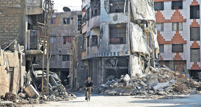A man riding a bicycle through buildings claimed to be damaged by Russian airstrikes in the Douma neighborhood of Damascus, Syria.