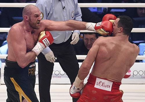 Britain's Tyson Fury, left, punches Ukraine's Wladimir Klitschko and in a world heavyweight title fight for Klitschko's belts