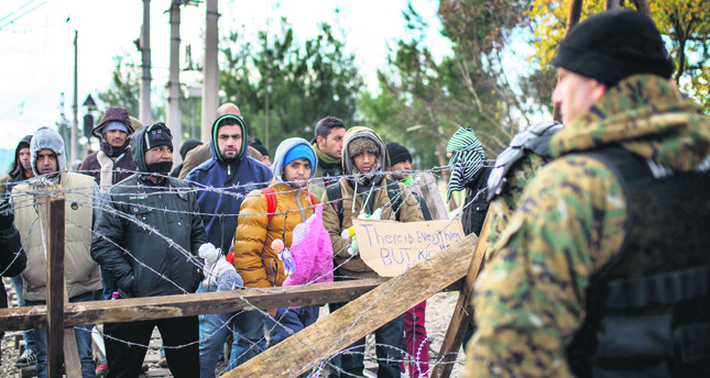 Migrants demonstrate in front of Macedonian police as they wait to cross the Greek-Macedonian border near Gevgelija.