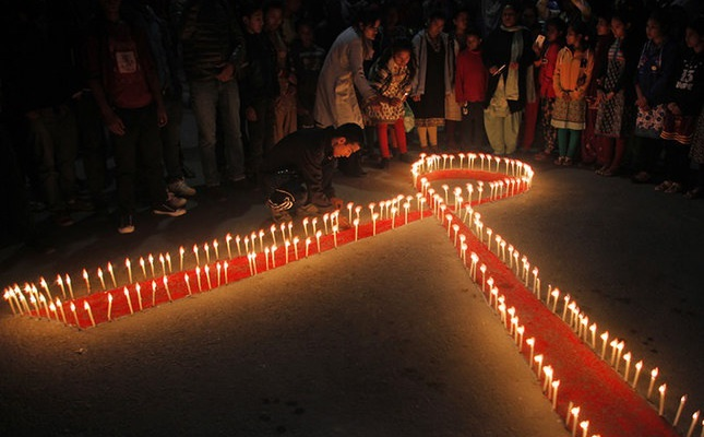 """Nepalese women and children from """"Maiti Nepal"""", a rehabilitation center for victims of sex trafficking, light candles on the eve of World AIDS Day, observed on Dec. 1 every year, in Kathmandu, Nepal, Nov. 30, 2015. (AP Photo)"""