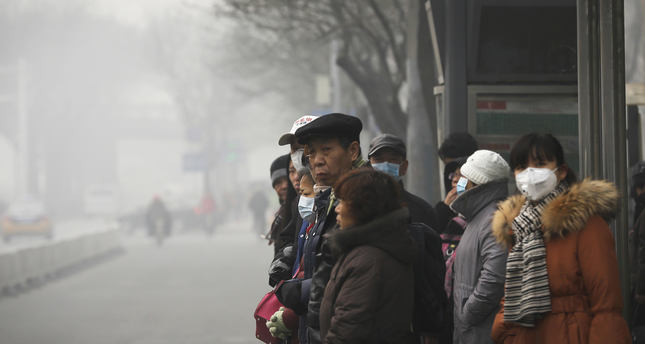 Commuters, some wearing masks to protect themselves from pollutants, wait at a bus stand on a heavily polluted day in Beijing, Monday, Nov. 30, 2015. (AP Photo)
