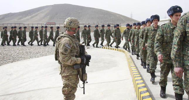 A U.S. soldier, left, watches members of the Afghan Public Protection Force arrive at the transition ceremony of private security forces on March 2012. (AP Photo)