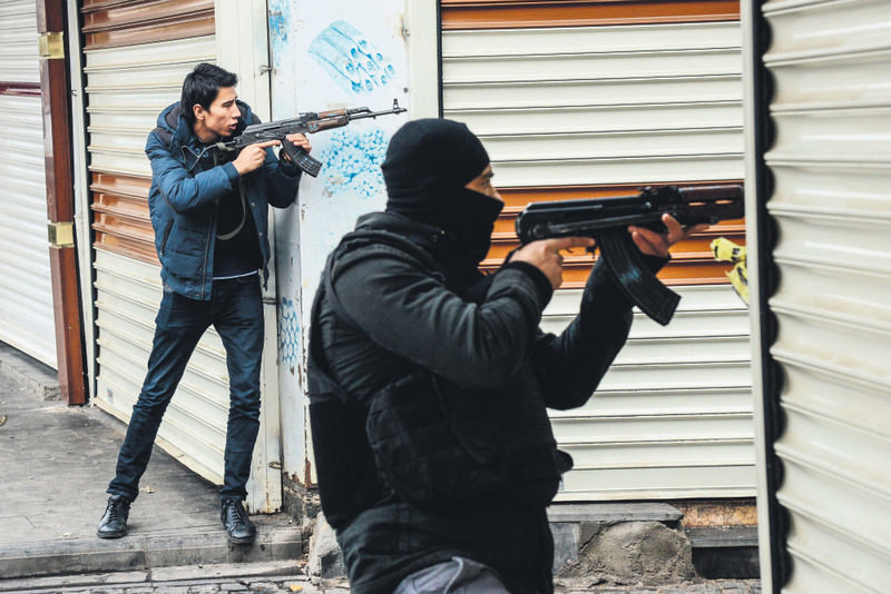 A plainclothes police officer and a special forces officer point their guns toward the street where Tahir Elu00e7i was killed. Officers were deployed in the area after a forensics team examining the scene came under fire yesterday.