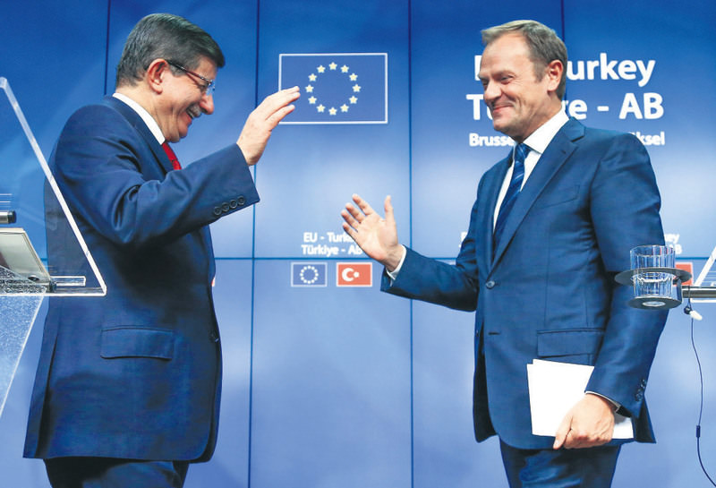 Prime Minister Davutou011flu (L) and European Council President Tusk greet each other after a news conference following a EU-Turkey summit in Brussels on Sunday.