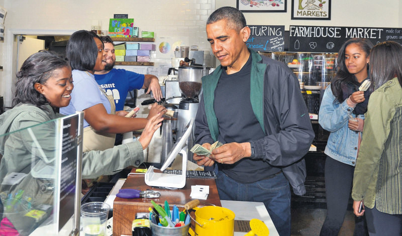 U.S. President Barack Obama (C) pays for purchases at Pleasant Pops, as daughters Malia and Sasha (R) enjoy a popsicle, in Washington D.C. in ,Small Business Saturday.,