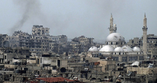 Smoke rises behind damaged buildings as the Khalid bin al Walid Mosque is seen on right in the besieged area of Homs March 9, 2014. (Reuters Photo)