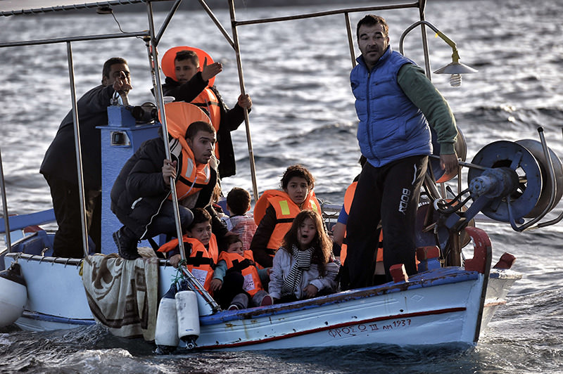 Greek fishermen rescuing Syrian refugees as the boat they boarded sank off Greek island of Lesbos after crossing Aegean sea from Turkey on Oct 30, 2015 (AFP photo).