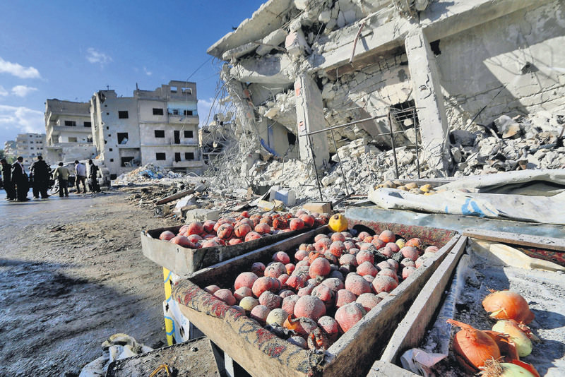 Products are covered in dust as people inspect a site claimed to be hit by airstrikes of the Russian air force on a busy marketplace in the town of Ariha, in Idlib province, Syria.