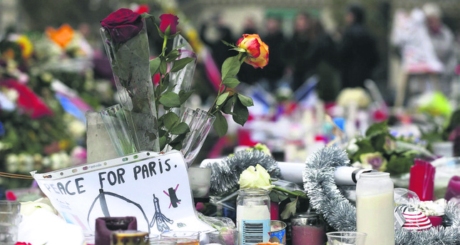 People leave French national flags, candles and flowers at a makeshift memorial in Paris for the 130 people who were killed in a terror attack, claimed by DAESH.