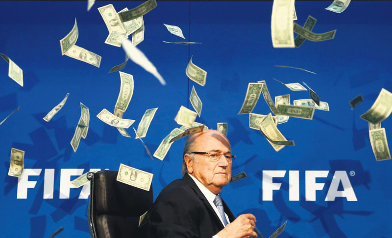 British comedian known as Lee Nelson (unseen) throws banknotes at FIFA President Sepp Blatter as he arrives for a news conference after the Extraordinary FIFA Executive Committee Meeting at the FIFA headquarters in Zurich, Jul. 20, 2015.