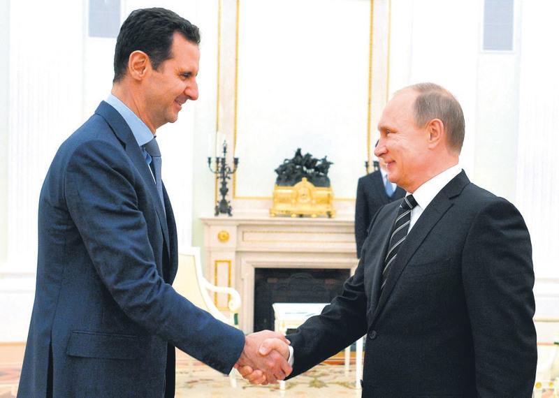 Russian President Vladimir Putin (R) shakes hand with Syria's Bashar al-Assad in the Kremlin in Moscow on Oct. 20.