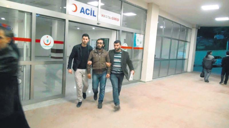 Two police officers escort Muhammad al-Rasheed after a medical examination following his arrest in u015eanlu0131urfa in March.