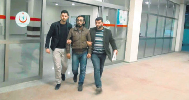 Two police officers escort Muhammad al-Rasheed after a medical examination following his arrest in Şanlıurfa in March.