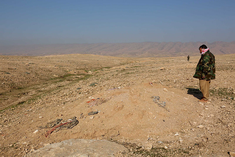 A member of the peshmerga forces inspects bones, suspected to belong to members of Iraq's Yazidi community, are seen at mass grave in Sinjar, Nov 30, 2015 (Reuters photo)