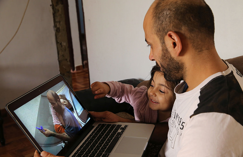 In this picture taken on Saturday, Nov. 28, 2015, Abdul Halim al-Attar, a refugee from Syria sits next his daughter Reem, 4, as they look at a photo on a laptop during an interview with The Associated Press (AP Photo)
