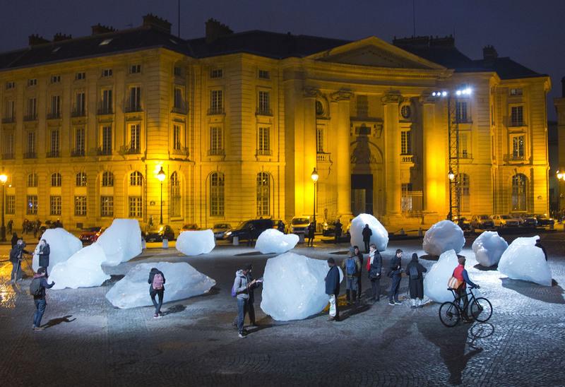 Visitors walks through ice blocks part of the sculpture ,Ice Watch,, by Danish artist Olafur Eliasson, Thursday Dec. 3 2015 in Paris. (AP Photo)