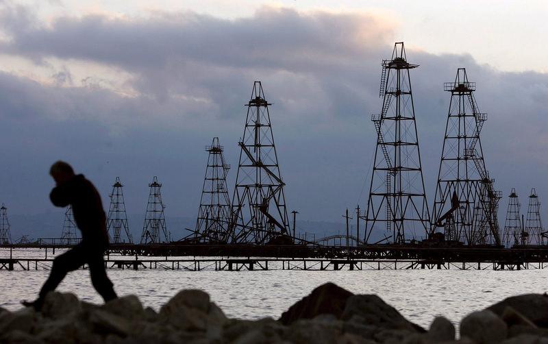 A file photo dated 07 October 2005 showing a worker walking in front of the oil derricks on the Caspian Sea near Baku, Azerbaijan. (EPA Photo)
