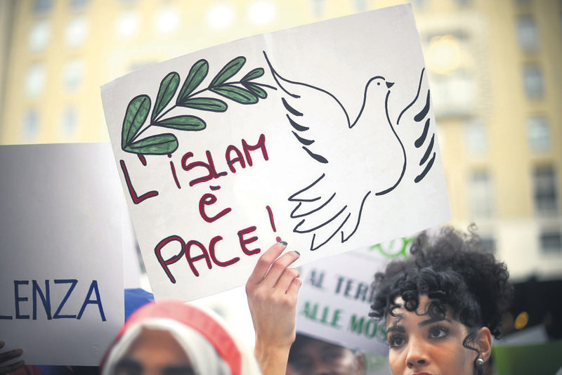 A woman shows a poster reading ,Islam is peace, during a demonstration of Muslims speaking out against terrorism.