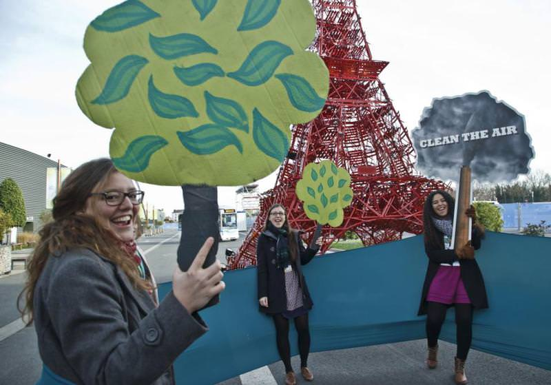 Representatives of NGOs hold cut out of trees and shout,clean the air, plant a tree,, at the COP21, UN Climate Change Conference, in  Paris, Dec. 5, 2015.  (AP Photo)