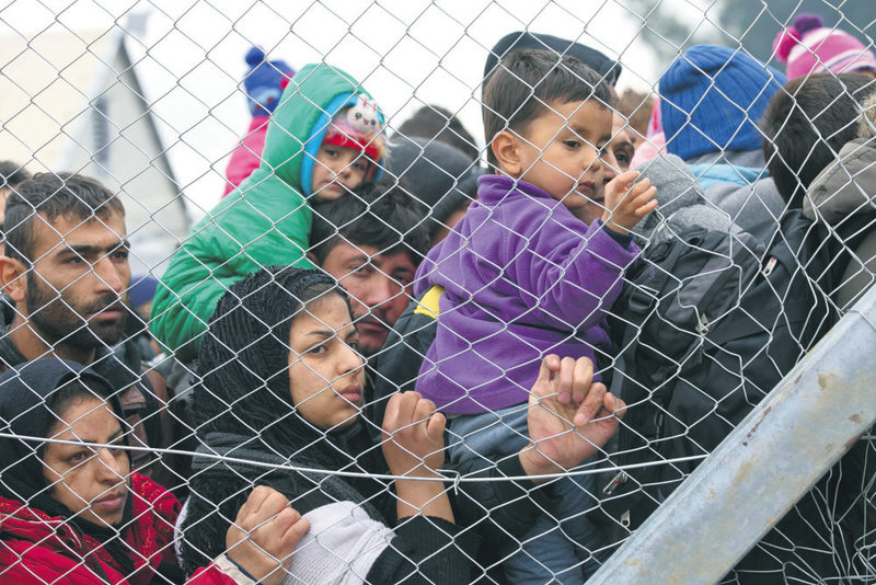 Stranded migrants awaiting entry into Macedonia on the Greek side of the border were photographed through a fence from the Macedonian side of the border