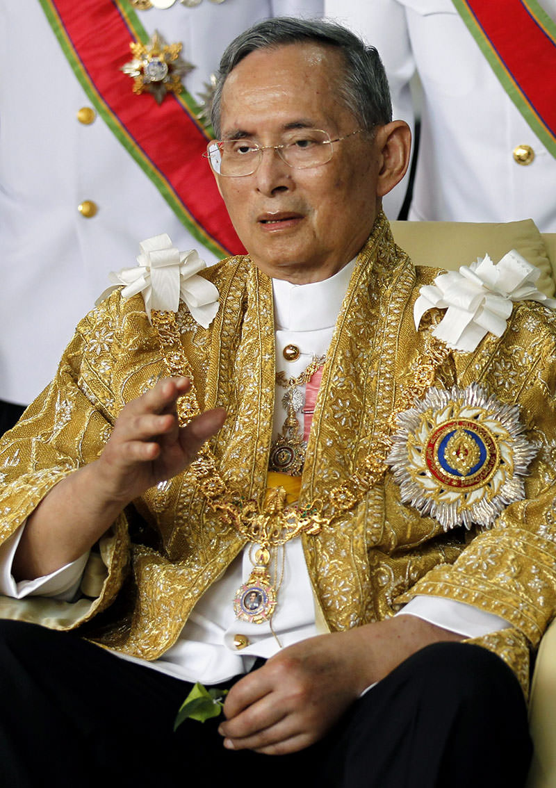 King Bhumibol Adulyadej waves to well-wishers as he sits in wheelchair after returning from royal ceremony marking his 84th birthday at Siriraj Hospital in Bangkok, 05 Dec 2011 (EPA photo)