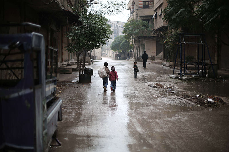 Syrian children walk in the rain in the town of Saqba, on the outskirts of the capital Damascus, on November 17, 2015 (AFP photo)