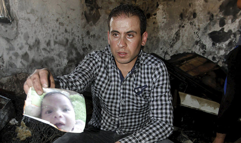 A relative of 18-month-old Palestinian baby Ali Dawabsheh, who was killed after his family's house was set to fire in a suspected attack by Jewish extremists, shows his picture at the burnt house (Reuters Photo)