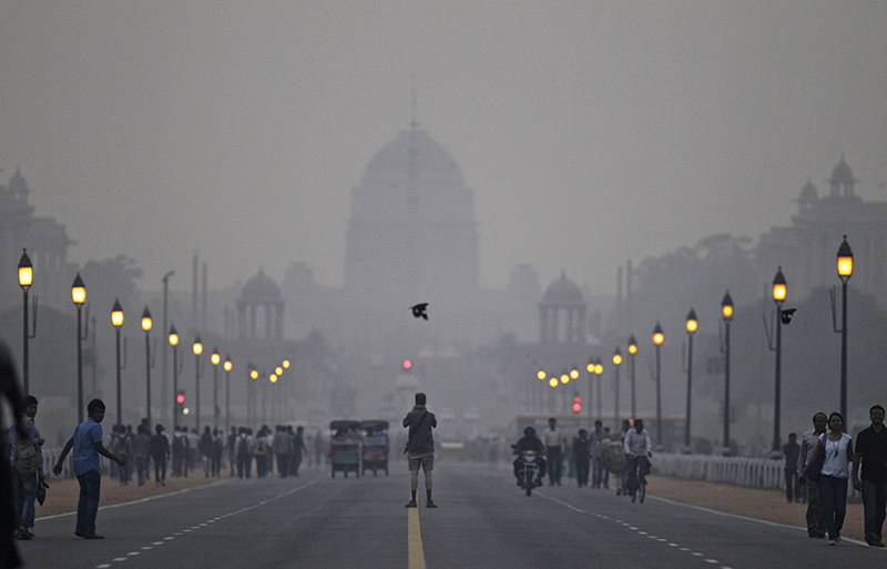 In this Nov. 3, 2012 file photo, a tourist stands in the middle of a street in front of the Presidential Palace enveloped in a blanket of smog, caused by a mixture of pollution and fog, in New Delhi (AP Photo)