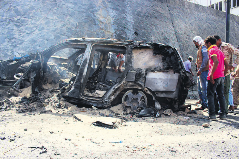 People inspect the scene of a car bomb attack that killed a Yemeni senior official in the southern port city of Aden, Yemen.