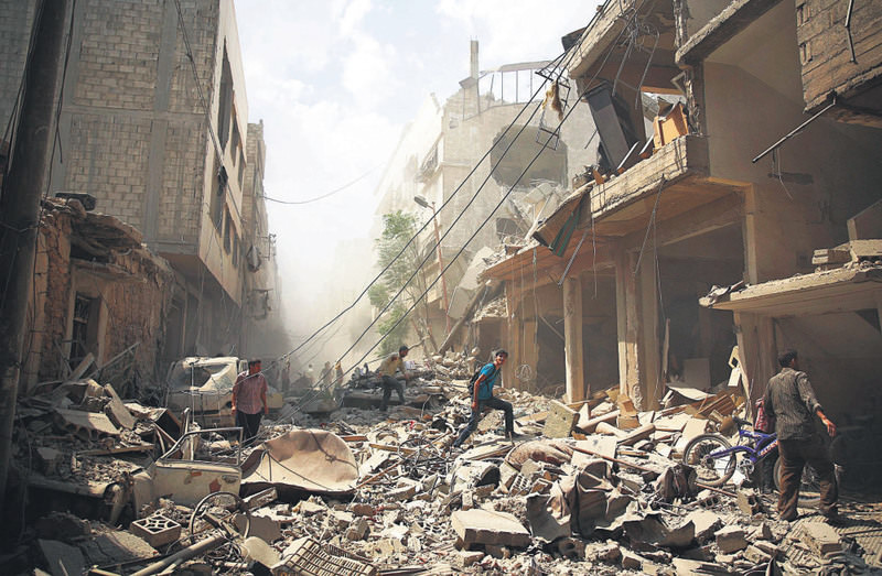 Syrians walk amid the rubble of buildings destroyed following reported airstrikes by regime forces in the moderate-held area of Douma, east of the capital Damascus, Syria