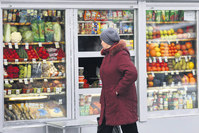 A Russian woman peers through a window to view fruits and vegetables at a street side market in Moscow. The Russian government banned fruits and vegetables imported from Turkey.