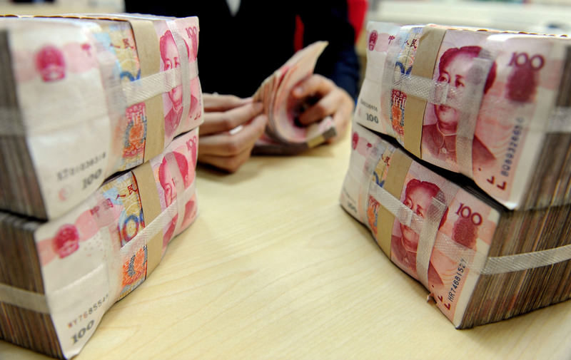A file picture dated 13 January 2010 of a bank teller counting renminbi bank notes in Shenyang, China. (EPA Photo)