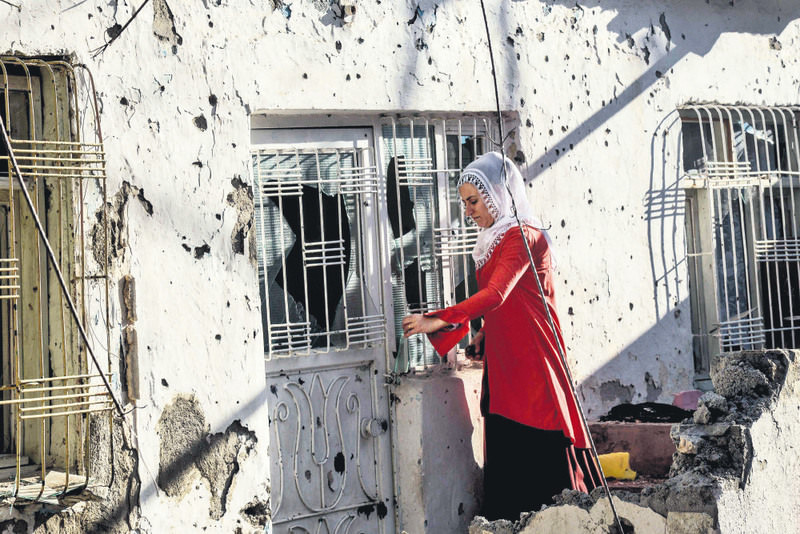A Kurdish woman trying to open the door of her home in Silvan, a southeastern district of Turkey, after clashes between security forces and Kurdish militants