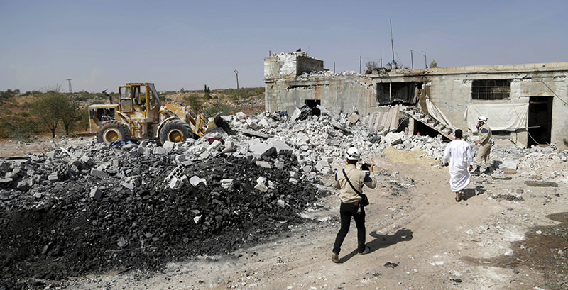 Civil defence members walk next to a site hit by what activists said were airstrikes carried out by the Russian air force at Ehsim town in the southern countryside of Idlib, Syria October 3, 2015 (Reuters Photo)