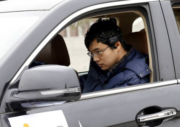 Researcher Zhang Zhao wearing a brain signal-reading equipment prepares to move a car with his brain wave, during a demonstration at Nankai University in Tianjin, China, November 17, 2015.